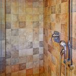 Luxurious walk-in shower, features rich floor-to-ceiling tile work, rain shower head, and body shower fixture - including quality GROHE Shower Valve  and KWC Mixing Valve.