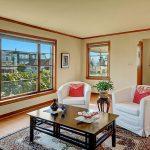 Welcome home! The living room basks in natural light, boasting original wood-trimmed picture windows, gleaming oak hardwood floors...