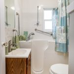 The bright main floor bath has a newer walk-in bathtub.