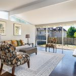 In the style of Pacific Northwest mid-century architect Paul H. Kirk, this home embraces 'bringing the outside in' with its soaring vaulted ceilings and a full-width west wall of windows basking the living and dining rooms in natural light...