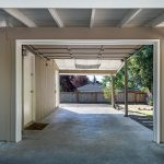 The attached carport with garage door provides a storage closet and easy access into the kitchen for groceries.