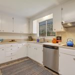 The bright white kitchen features ample cabinetry storage and counter space, and...