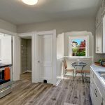 A bright, open kitchen boasts new flooring, countertops, stainless appliances, LED lighting, and...