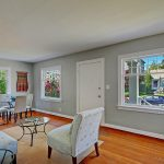 """Bright and welcoming, the large front living and dining room features original oak floors, period windows, and 8'3"""" ceilings."""