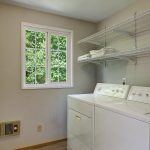 Upstairs laundry room is super convenient! It's oversized, with shelving for your linens and a brand-new floor.