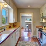 The galley kitchen features stainless appliances, original tile counters, Pergo flooring, and plenty of cabinet space.