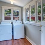 From the breakfast nook find this bright laundry room with walls of windows in the side patio and back yard.