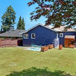 The large sunny fenced back yard is ideal for gardening, play, and has paved alley access.
