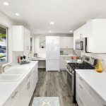 The bright, spacious kitchen with a wrap-around eating bar offers plenty of counters and cabinet space, new luxury vinyl flooring, stainless gas range, built-in desk, pantry, and back deck access.