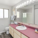 The modest main bathroom serves the floor, with plenty of counters and cabinet space. Plenty of room to accommodate a future double-vanity. New luxury vinyl floor was recently installed here as well.
