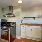 The kitchen features a Bosch gas range, stainless appliances and shelving, oak counters, newer quality wood cabinetry and hardware, and peaceful views of the back yard, city, and bay.