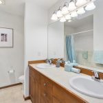 This sky-lit full bath serves the other two quiet bedrooms on the floor, also with a double vanity for efficiency.